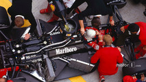 Alain Prost sits in his McLaren MP4-3 TAG Porsche while the mechanics get to work on the car and refuel