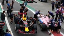 The car of Max Verstappen, Red Bull Racing RB13 and Esteban Ocon, Sahara Force India VJM10 are pushed by mechanics